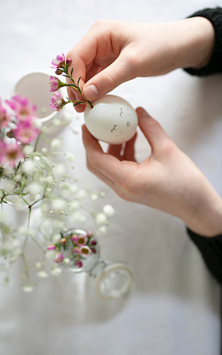 Arranging flowers in blown egg