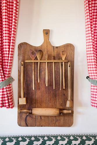 Wooden board repurposed to store kitchen utensils