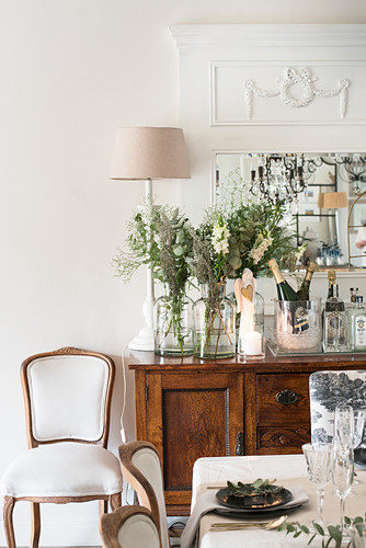 Flowers and Champagne on festive sideboard seen across dining table