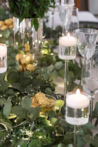 Festive candlesticks and eucalyptus branches on Christmas table