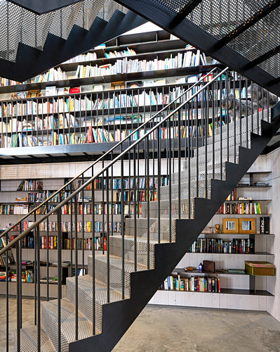 Self-supporting staircase made from perforated metal in front of bookcase