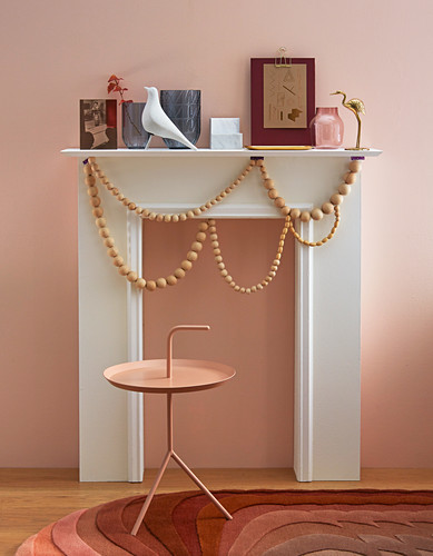 Faux fireplace decorated with garlands of wooden beads