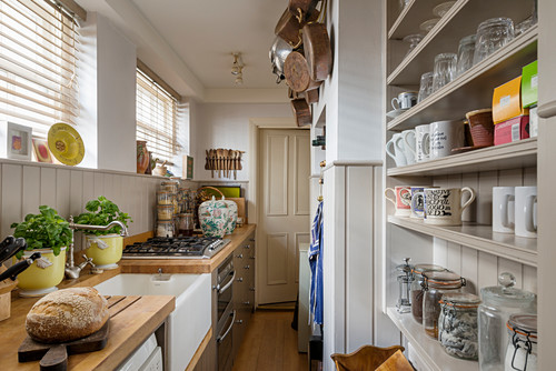 Narrow, country-house-style kitchen with wainscoting