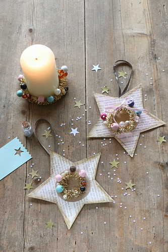 Christmas stars handcrafted from coloured book pages decorated with beads and glitter