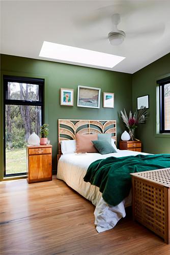 Schlafzimmer in Naturtönen mit grünen Wänden und Blick auf Bäume