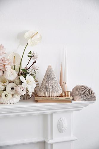 Weißes Blumengesteck, Papierdekoration und Kerzen auf Kaminsims