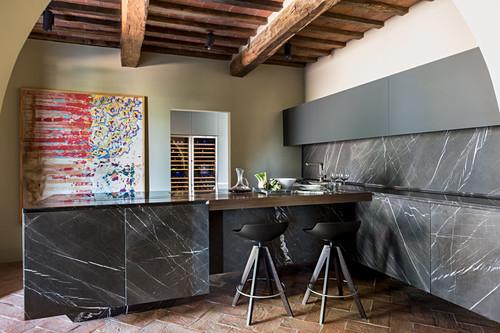 Moderne Küche mit schwarzem Marmor und rustikalen Balken