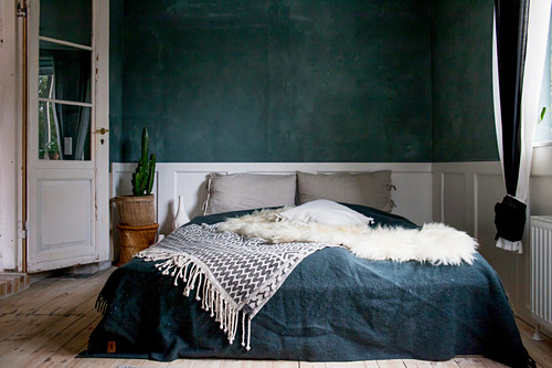 Double bed against dark wall with white wooden wainscoting