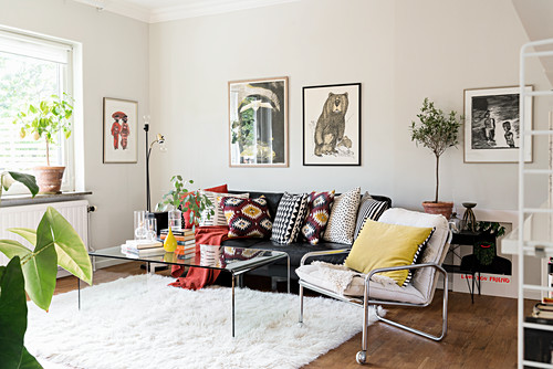 Colourful scatter cushions on leather sofa and armchair in living room
