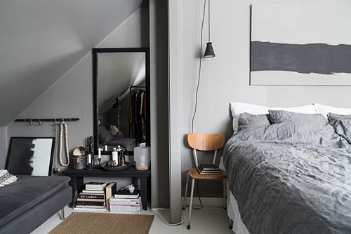 Sofa under sloping ceiling in grey bedroom