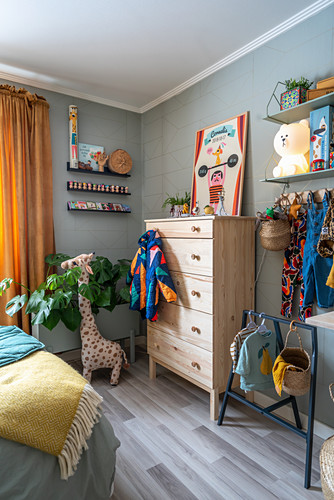 Baby clothes and chest of drawers in room with pale grey walls