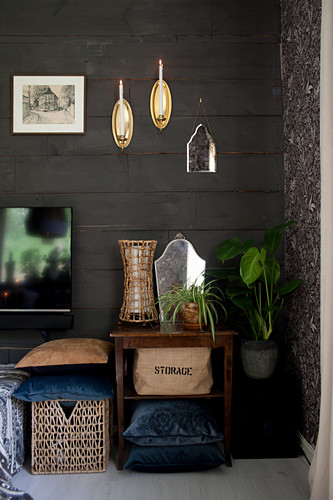 Table, basket, cushions and plants on floor below decorations on black board wall