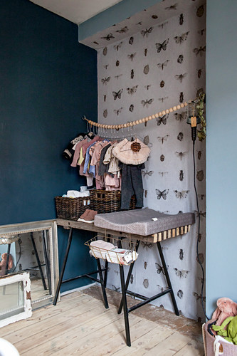 Changing table below clothes rail in nursery with butterfly-patterned wallpaper