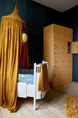 Nursery with blue walls, ochre-yellow accents and pale wooden floor