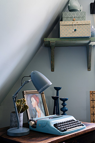 Typewriter and vintage accessories on table below sloping ceiling