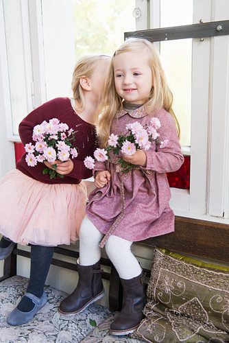 Two girls holding flowers and whispering