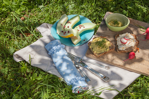 Hand-sewn cutlery roll, plate of honeydew melon and open-faced sandwiches on board