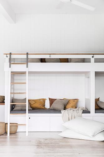 Etagenbetten im Zimmer mit weißer Holzverkleidung