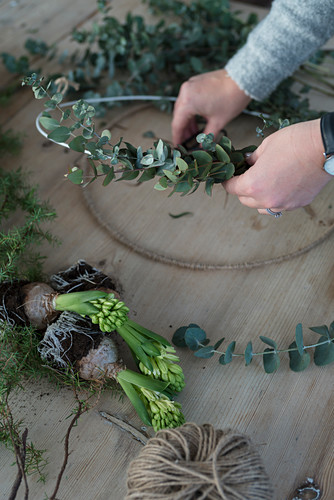 Tying a wreath of eucalyptus leaves and hyacinths