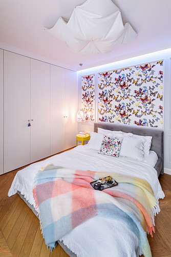 Butterfly wallpaper behind bed in bedroom with fitted wardrobes