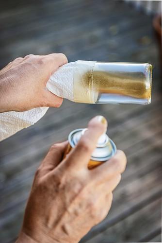 Glasflasche wird mit Goldfarbe besprüht