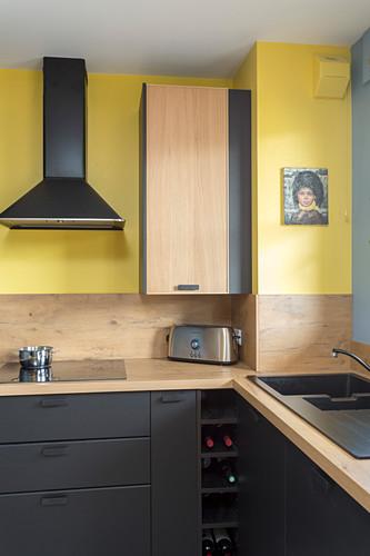 Moderne Küche in Schwarz und Gelb und mit Holz