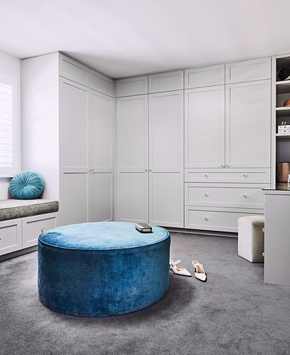 Blue velvet pouf in walk-in closet with cassette fronts