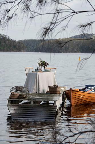 Gedeckter Tisch auf einem Steg und Boot auf einem See