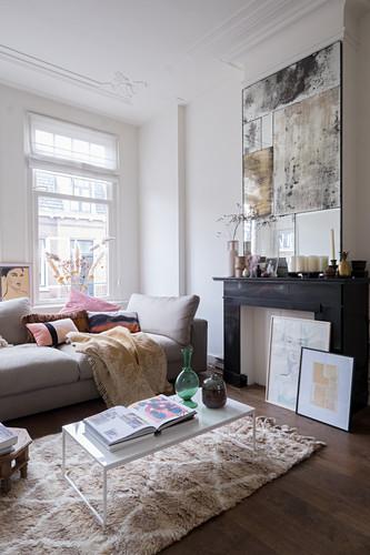 Helles Sofa im Wohnzimmer mit stillgelegtem Kamin, darüber Kunstwerk