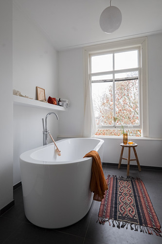 Free-standing bathtub in bathroom with window