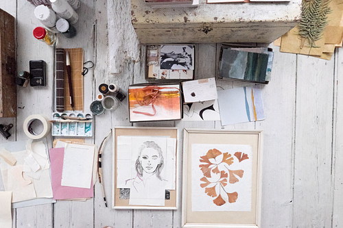 Pictures and painting utensils on white wooden floor