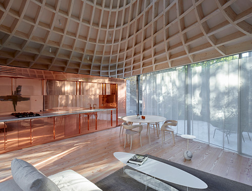 Lounge, copper kitchen, glass walls and funnel-shaped ceiling in open-plan interior