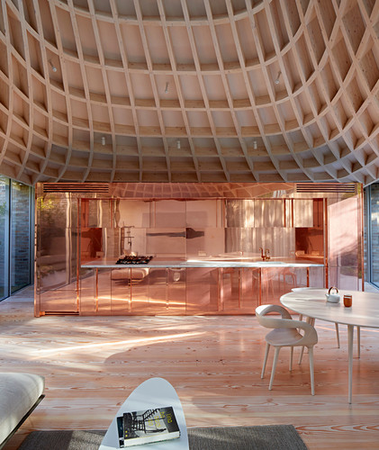 Lounge, copper kitchen and funnel-shaped ceiling in open-plan interior
