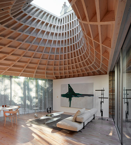 Minimalistisches Wohnzimmer in modernem Anbau mit Verglasung und trichterförmigem Dach