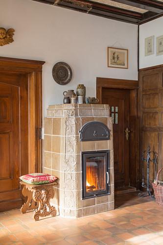 Kachelofen mit brennendem Feuer zwischen Holztüren