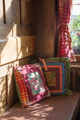 Bank mit bunten Kissen in sonniger Bauernstube