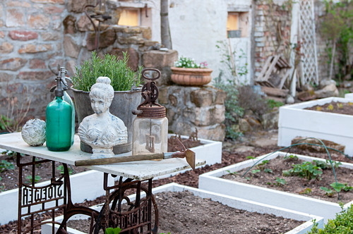 Bust of woman and vintage bottles on table next to freshly prepared raised beds in garden