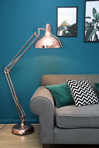 Grey sofa and standard lamp in living room with petrol-blue wall