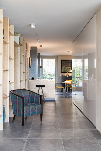 Armchair against floor-to-ceiling wooden shelves and white fitted cupboards in open-plan living space with tiled floor