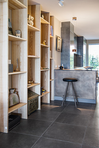 Floor-to-ceiling wooden shelves and breakfast bar in open-plan living space with tiled floor