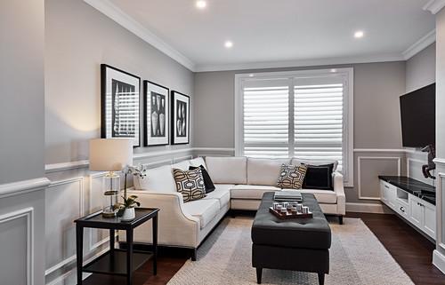 Corner sofa, ottoman and prints of sea shells in elegant living room