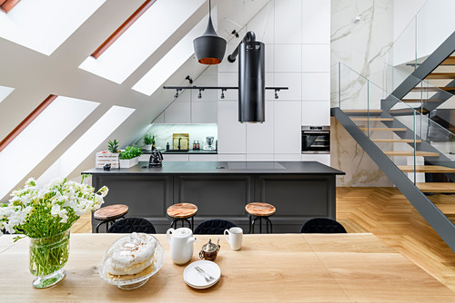 View across dining table to island counter and stairs in high-ceilinged room with skylights in sloping wall
