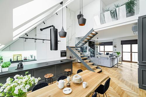Kücheninsel und Essbereich, im Hintergrund Treppe und Lounge in hohem Raum mit Dachschräge
