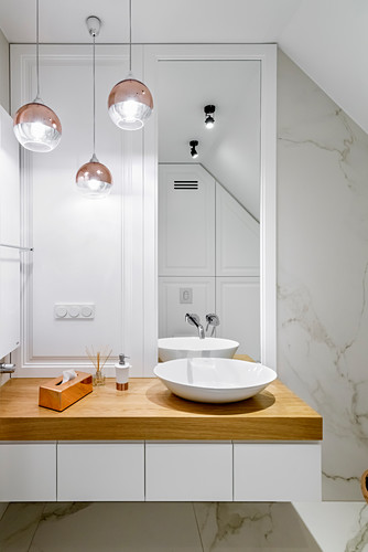 Washstand with countertop sink in elegant bathroom with marble wall