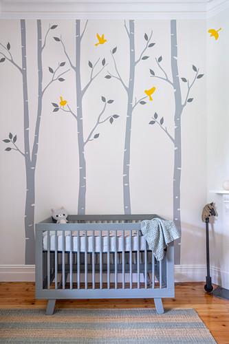 Blaues Gitterbettchen in Babyzimmer mit fröhlicher Wandmalerei