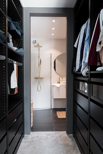 View through walk-in wardrobe into modern bathroom with shower and washstand
