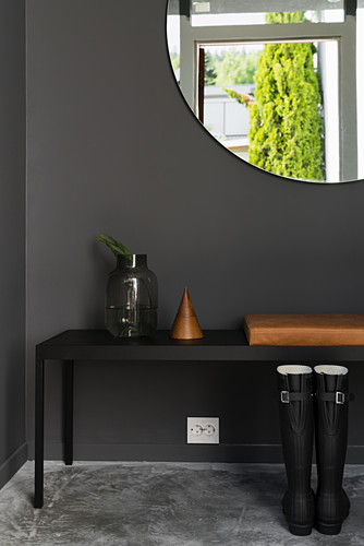 Bench below large round mirror on black wall in hallway