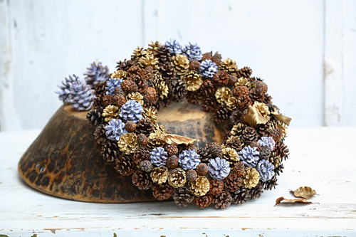 Simple and elegant winter wreath of pine cones painted gold and dipped in coloured wax