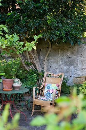 Rattan armchair against stone wall in Mediterranean garden