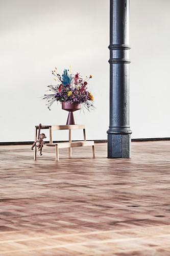 Vase of flowers on bench next to metal pillar